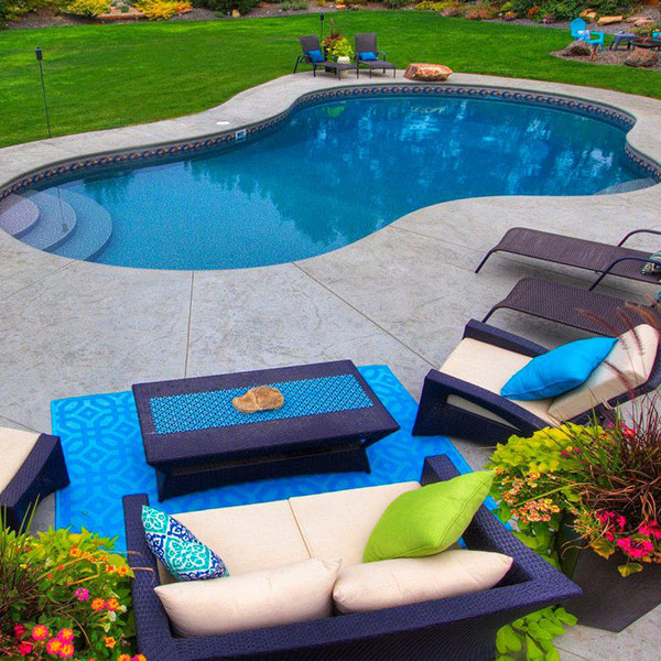 Beautiful ergonomic pool in a bright yard, surrounded by comfortable deck chairs.